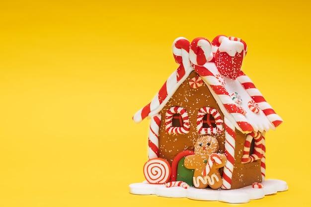 Casa giocattolo di natale con omino di pan di zenzero su sfondo giallo