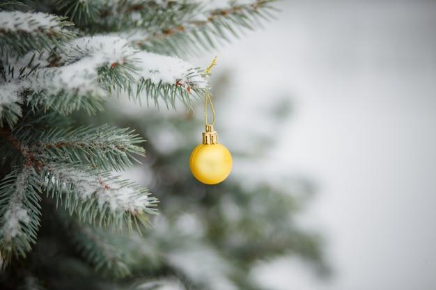 Giocattolo di natale sull'albero di natale nevoso. sfondo di natale