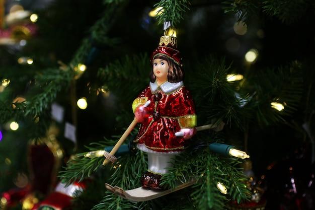 Giocattolo di natale sul ramo di abete ragazza che scia con un vestito rossoconcetto di festa