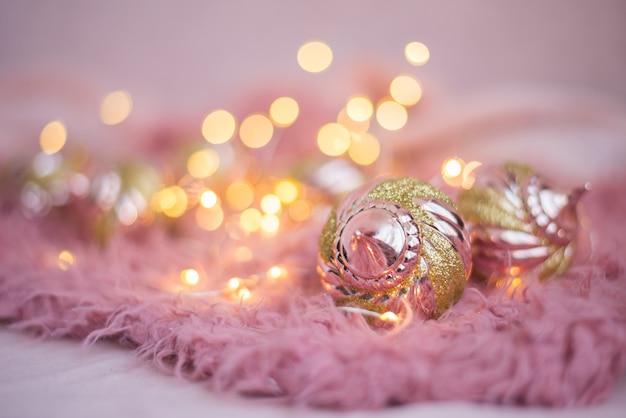 Giocattoli di natale colori rosa e oro su luci natalizie su una soffice coperta rosa