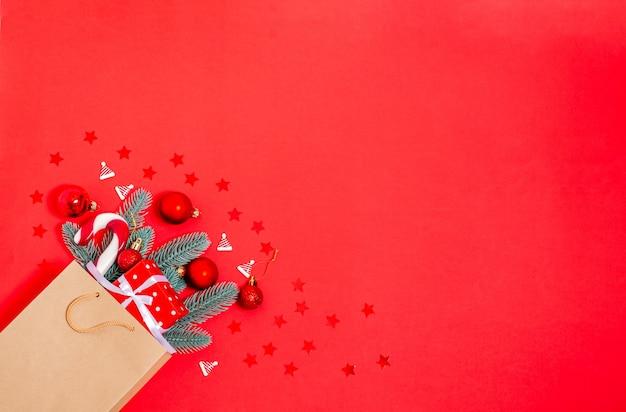 Giocattoli di natale, scatola regalo, rami di abete, canna di caramello in un sacchetto della spesa di carta su uno sfondo rosso. banner, modulo cartolina. copia spazio, piatto laici. capodanno, natale, 2021. vista dall'alto.