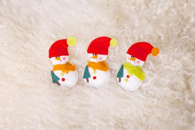 Giocattoli di natale - pupazzi di neve da un feltro su uno sfondo di pelliccia bianca. periodo natalizio. capodanno e vacanze invernali