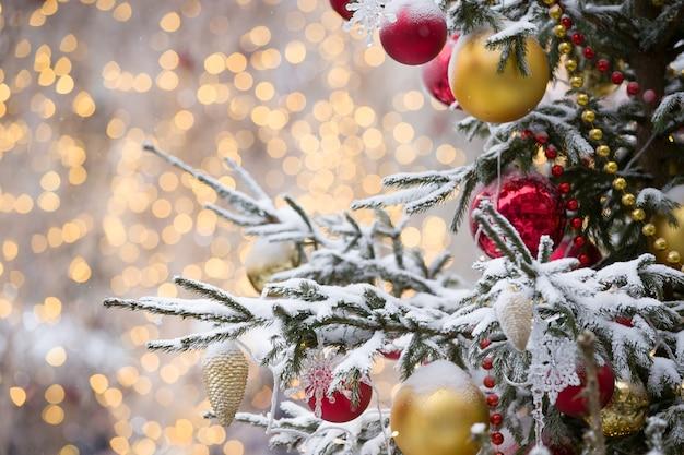 Giocattoli natalizi e ghirlande scintillanti pendono ricoperti di neve abete sempreverde