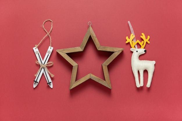 Giocattoli di natale sci in legno, cervo giocattolo di feltro bianco e stella cava in legno su sfondo rosso scuro.