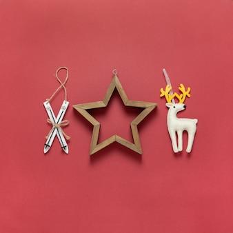 Giocattoli di natale sci di legno, cervo giocattolo di feltro bianco e stella vuota in legno su rosso scuro