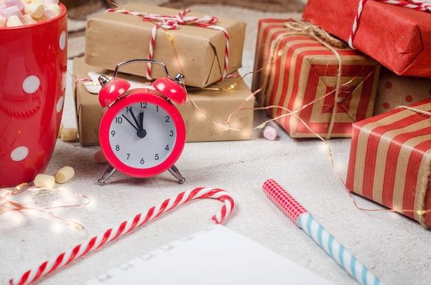 Regalo di decorazioni tradizionali natalizie per rami di albero su sfondo rosa pastello piatto disteso