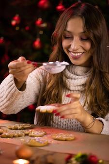 Tradizioni natalizie. giovane bella donna che fa i biscotti di natale spolverando pan di zenzero con zucchero in polvere. dessert artigianale di capodanno cucina, vacanza invernale a casa, concetto di cottura stagionale