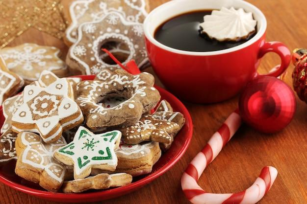 Dolcetti di natale sul piatto e tazza di caffè sul primo piano del tavolo di legno