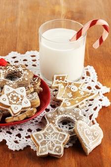 Dolcetti natalizi su piatto e bicchiere di latte sul primo piano del tavolo di legno