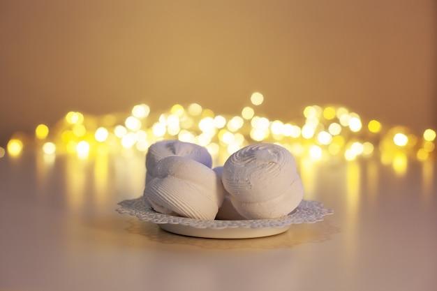 Dolcetti natalizi per babbo natale su sfondo di luci ghirlanda marshmallows