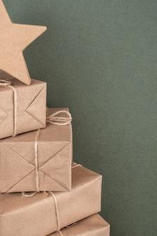 Albero di natale. scatole in carta artigianale su sfondo verde, primo piano. concetto di natale o capodanno. vista frontale copia spazio.