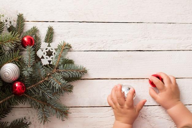 Ramo dell'albero di natale con le mani del bambino e della decorazione su fondo di legno bianco