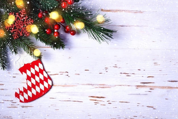 Ramo di albero di natale con decorazioni su fondo di legno bianco. Foto Premium