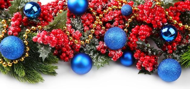 Ramo di albero di natale con bacche rosse e decorazioni su sfondo bianco
