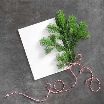 Ramo di albero di natale con carta bianca. disposizione piatta minima