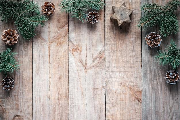 Rami di albero di natale pigne e stella di candela su fondo di legno