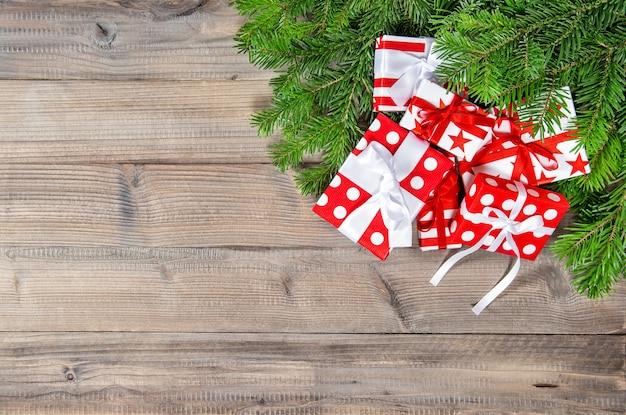 Rami dell'albero di natale e decorazione rossa dei regali su fondo di legno
