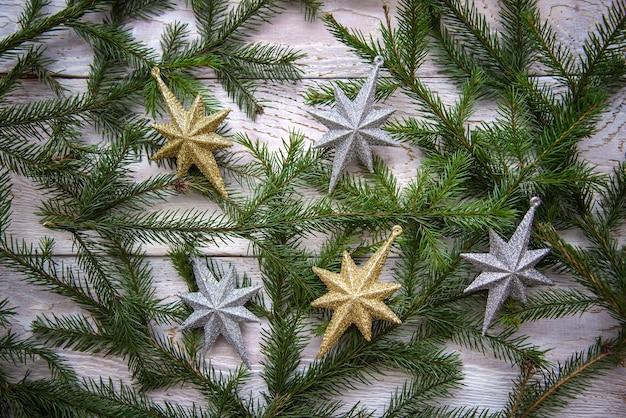 Rami di albero di natale e stelle su un fondo di legno bianco