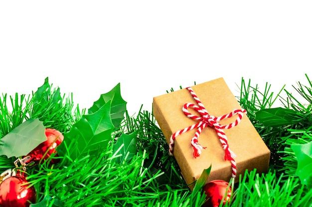 Rami di albero di natale con palline e regalo fatto a mano di carta da regalo kraft