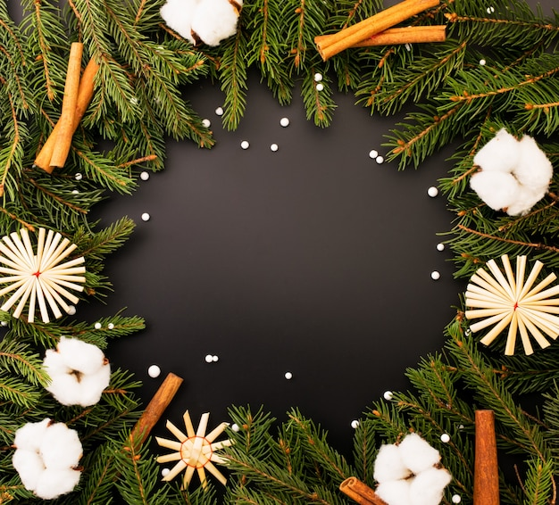 I rami degli alberi di natale con cotone, fiocchi di neve di paglia e cannella sono disposti in cerchio su uno sfondo nero, il luogo per il testo. sfondo di natale.