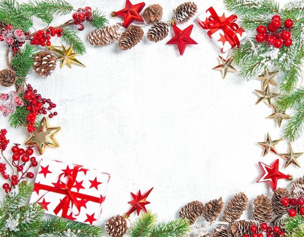 Rami di albero di natale con regali, stelle, decorazioni in oro rosso su sfondo bianco