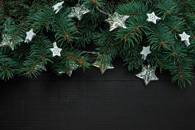 Rami di albero di natale con decorazioni di capodanno e stelle su un legno scuro