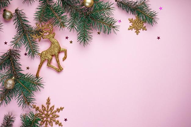 Rami di albero di natale, con ornamenti d'oro di capodanno e dolci multicolori sul rosa con copyspace, vista dall'alto.