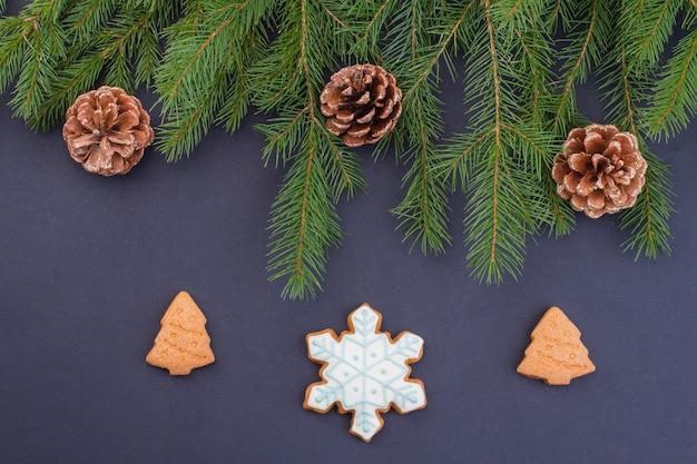 Rami di albero di natale con pigne e biscotti.