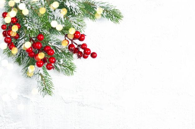 Rami di albero di natale con bacche rosse con decorazioni di luci dorate
