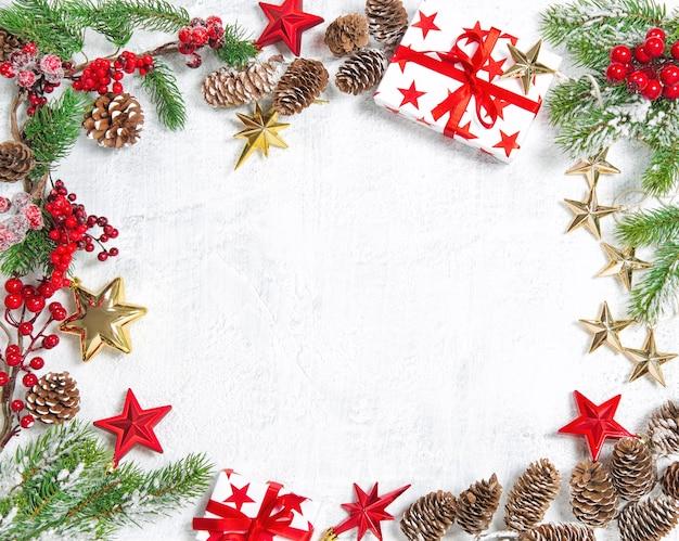 Rami di albero di natale con decorazioni in oro rosso su sfondo bianco