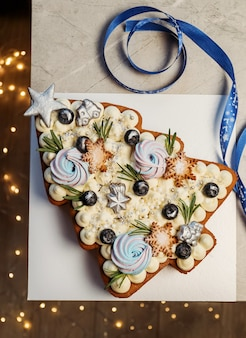 Torta dell'albero di natale. dolce regalo festivo, decorazioni con luci di capodanno.