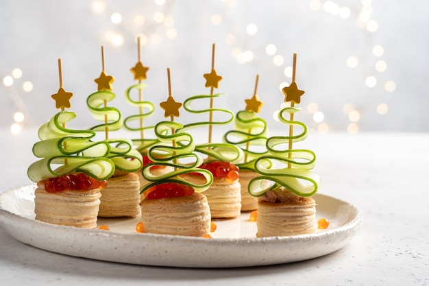 Canape dell'albero di natale con fetta di cetriolo, patè di salmone e caviale rosso per uno spuntino natalizio festivo