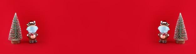 Albero di natale e statuetta in ceramica di bue in mascherina medica su sfondo rosso. ampio banner con copia spazio. simbolo del nuovo anno 2021.