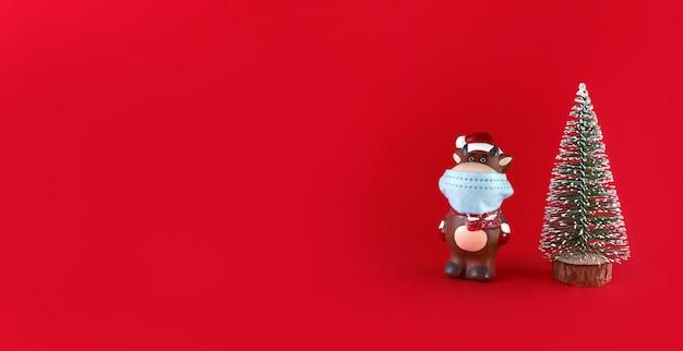 Albero di natale e statuetta in ceramica di bue in mascherina medica su uno sfondo rosso con spazio di copia. simbolo del nuovo anno 2021.