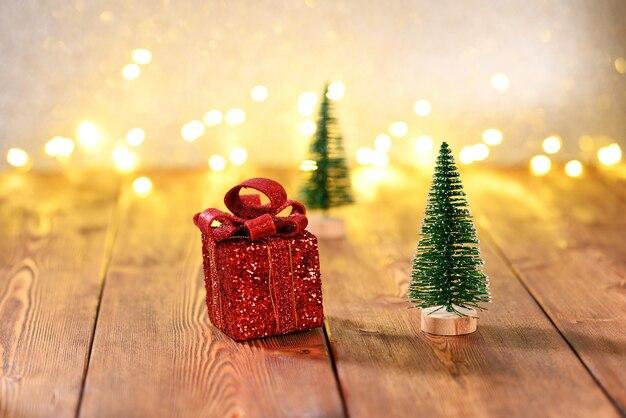 Albero di natale e regalo di natale su un tavolo di legno sullo sfondo di un boke