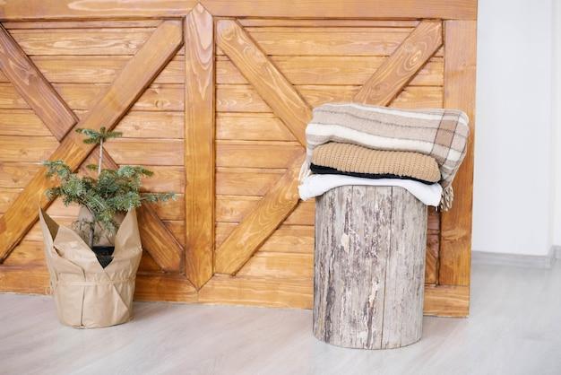 Albero di natale in una borsa artigianale e coperte sul ceppo.