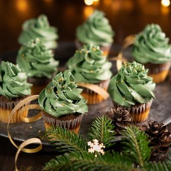 Il dessert dolce dei bigné dell'albero di natale con dorato spruzza su fondo di legno con il bokeh delle luci della ghirlanda. avvicinamento.