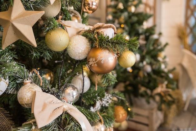 Di albero di natale decorato con perle, argento, cristallo, palline d'oro e giocattoli con parete bianca.