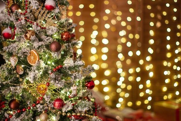Albero di natale decorato con giocattoli e ghirlanda luminosa. sullo sfondo illumina ghirlande