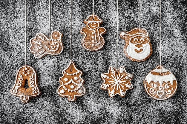 Biscotti del pan di zenzero della decorazione dell'albero di natale sui precedenti in polvere