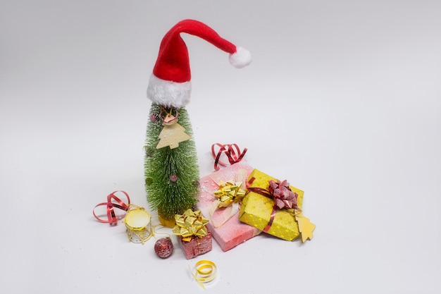 Albero di natale e decorazioni con lampada incandescente festiva, regali e fiocchi luminosi su sfondo bianco. composizione di natale e capodanno.