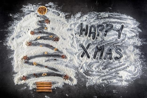 Albero di natale di farina con ornamenti anice stellato noci chicchi di caffè e bastoncini di cannella