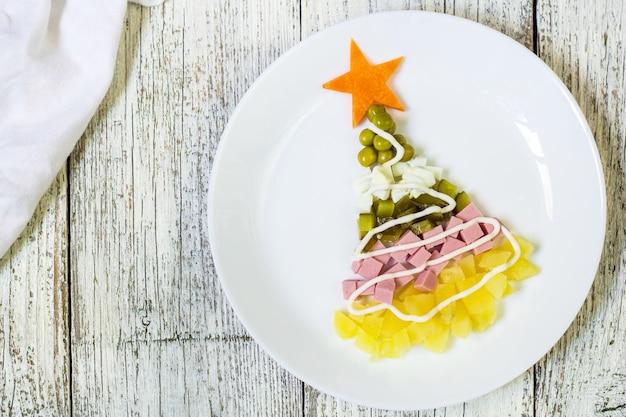 Albero di natale da un'insalata olivier nel piatto su una tavola di legno bianca. vista dall'alto con uno spazio di copia.