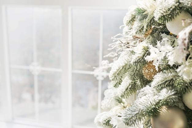 Albero di natale pieno di decorazioni e giocattoli alla finestra luminosa.