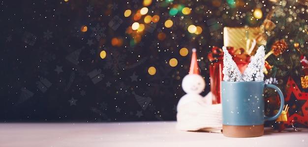 Albero di natale e confezione regalo sulla tazza con sfondo chiaro festival bokeh