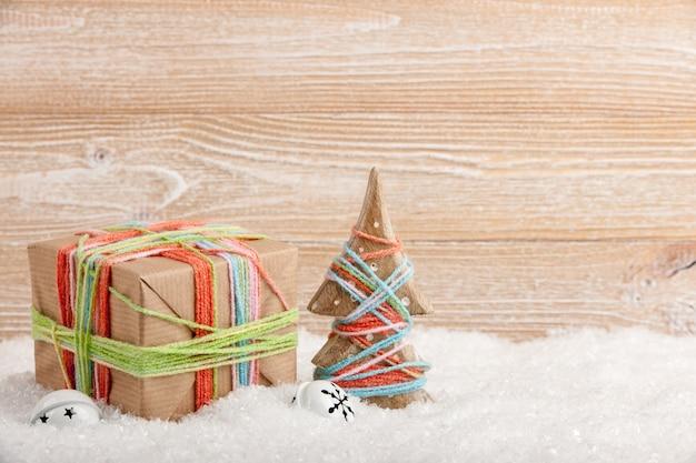 Albero di natale e confezione regalo sulla neve