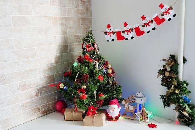Albero di natale, regali e decorazioni a casa sul tavolo bianco in cucina