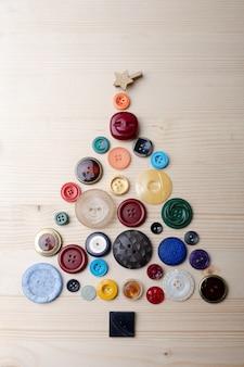 Un albero di natale faceva bottoni sul tavolo di legno