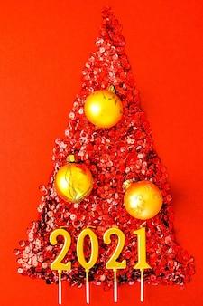 Albero di natale fatto da coriandoli lucidi su sfondo rosso. candele d'oro anno 2021. biglietto di auguri di capodanno e buon natale. concetto di vacanza