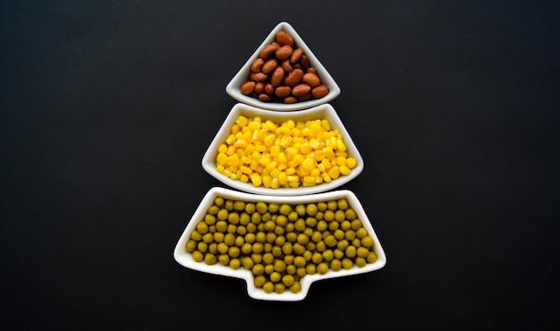 Albero di natale fatto di mais, piselli, fagiolini. vista dall'alto